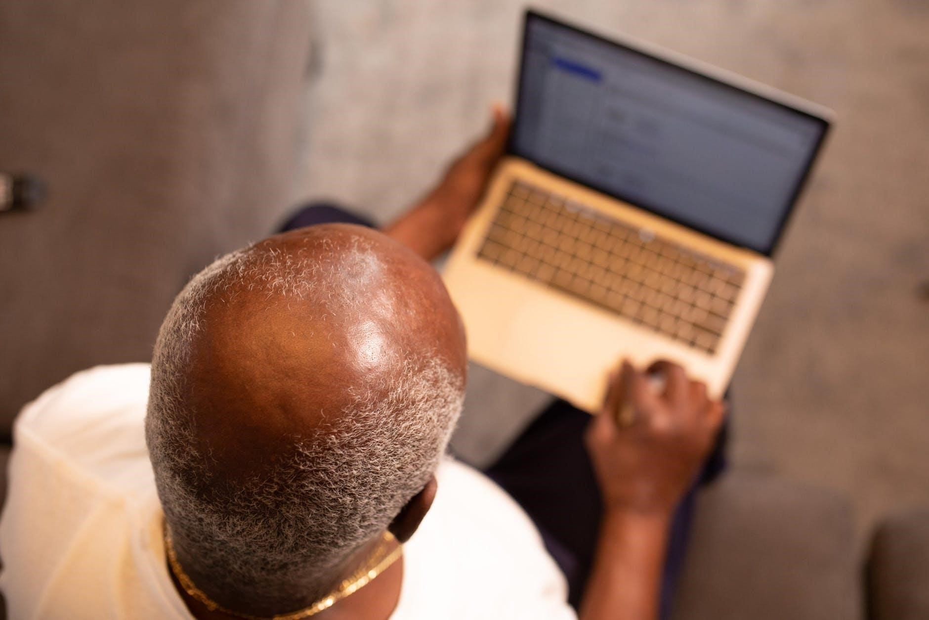 Bald man sitting in front a computer