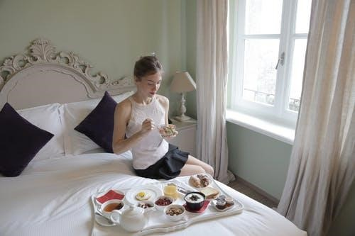 Girl sitting on the bed eating